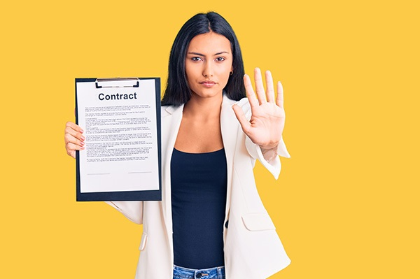 A woman holding up a contract in her right hand uses her left to signal pause.