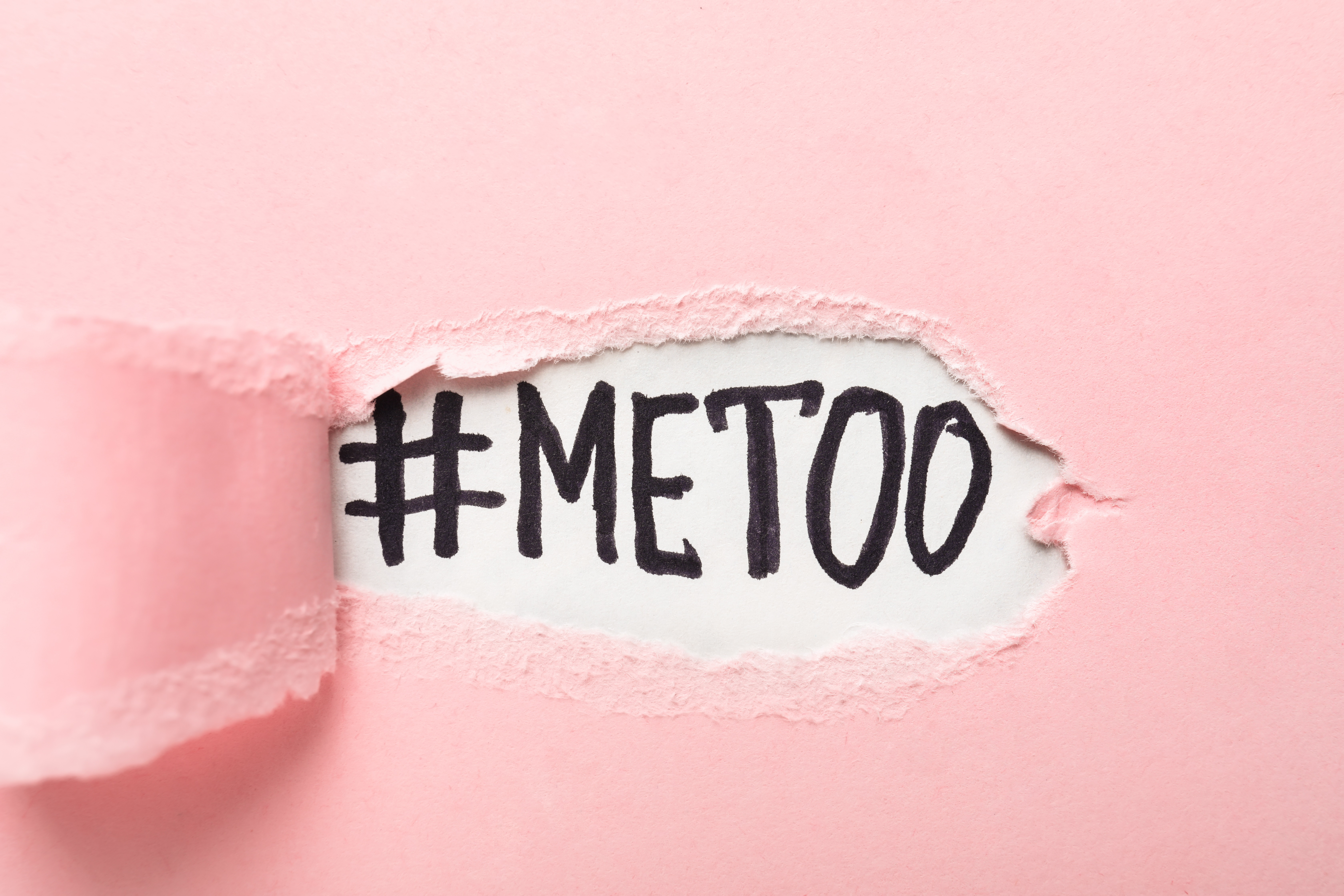 A pink page ripped open reveals #METOO in black ink on a white page.